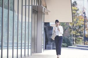スマホを持ち屋外を歩くビジネスウーマンの写真素材 [FYI04773160]