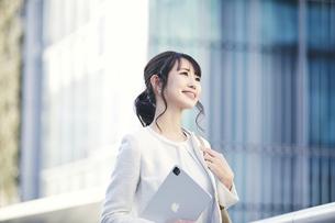 タブレットPCを持ち屋外を歩くビジネスウーマンの写真素材 [FYI04773161]