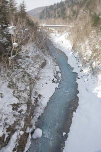 山の谷間を流れる冬の青い川の写真素材 [FYI04773318]