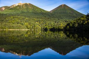 オンネトーから望む雌阿寒岳と阿寒富士、水面の鏡面反射の写真素材 [FYI04773706]
