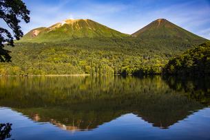 オンネトーから望む雌阿寒岳と阿寒富士、水面の鏡面反射の写真素材 [FYI04773719]