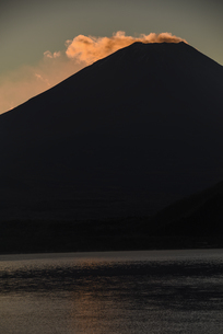 朝日に照らされる富士山頂部の雲と本栖湖の写真素材 [FYI04773802]