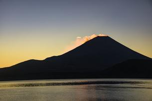 朝日に照らされる本栖湖と雲、富士山のシルエットの写真素材 [FYI04773805]