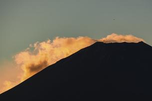 朝日に照らされる富士山頂部の雲と飛行機の写真素材 [FYI04773806]