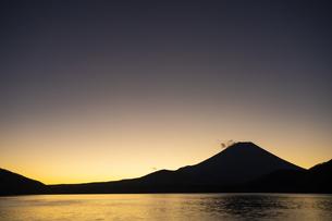 朝日に照らされる本栖湖と富士山のシルエットの写真素材 [FYI04773812]