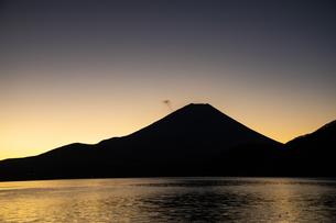 朝日に照らされる本栖湖と富士山のシルエットの写真素材 [FYI04773842]
