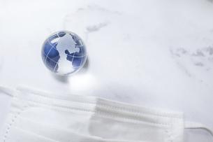 マスクと地球。新型コロナウイルス(COVID-19)や感染症の予防対策イメージ。の写真素材 [FYI04774307]