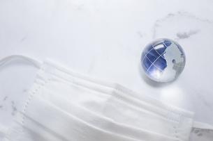 マスクと地球。新型コロナウイルス(COVID-19)や感染症の予防対策イメージ。の写真素材 [FYI04774308]