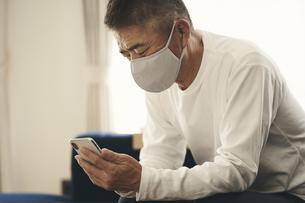 マスクをつけてスマートフォンを見る日本人シニア男性の写真素材 [FYI04774424]