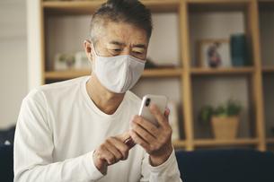 マスクをつけてスマートフォンを見る日本人シニア男性の写真素材 [FYI04774425]