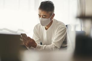 マスクをつけてスマートフォンを見る日本人シニア男性の写真素材 [FYI04774426]