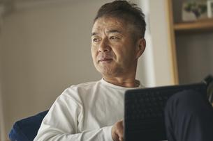 タブレットPCを持つ日本人シニア男性の写真素材 [FYI04774431]