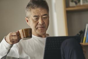 コーヒーを飲みながらタブレットPCを見る日本人シニア男性の写真素材 [FYI04774433]
