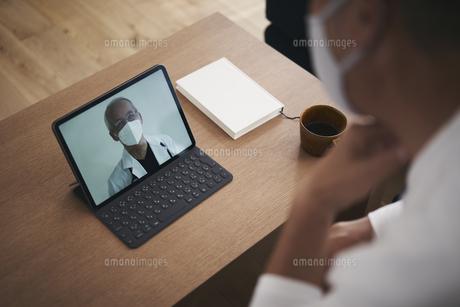 医師とテレビ電話で話す男性患者の写真素材 [FYI04774435]