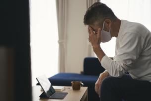 タブレットPCを見るマスクをつけた日本人シニア男性の写真素材 [FYI04774436]
