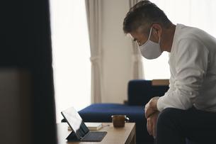 タブレットPCを見るマスクをつけた日本人シニア男性の写真素材 [FYI04774437]