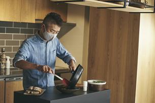 マスクをつけて料理をする日本人シニア男性の写真素材 [FYI04774447]