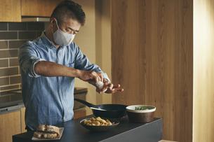マスクをつけて料理をする日本人シニア男性の写真素材 [FYI04774448]