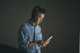 スマートフォンで音楽を聴く日本人シニア男性の写真素材 [FYI04774450]