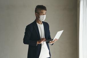 マスクをつけてノートパソコンを持つ日本人シニア男性の写真素材 [FYI04774455]