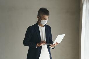 マスクをつけてノートパソコンを見る日本人シニア男性の写真素材 [FYI04774456]