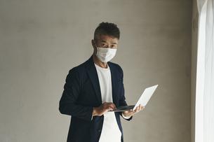 マスクをつけてノートパソコンを持つ日本人シニア男性の写真素材 [FYI04774457]