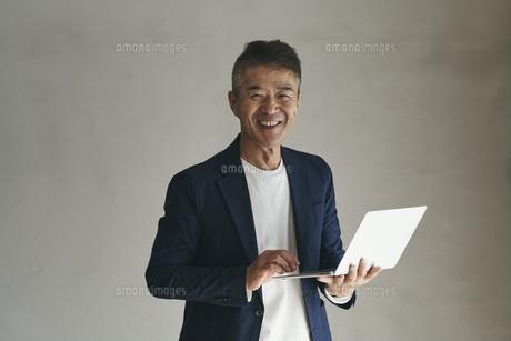 ノートパソコンを持つ日本人シニア男性の写真素材 [FYI04774458]