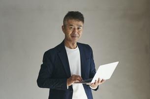 ノートパソコンを持つ日本人シニア男性の写真素材 [FYI04774459]