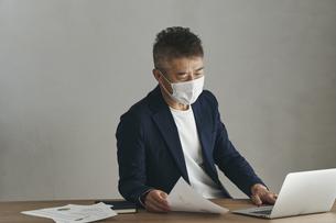 マスクをつけて仕事をする日本人シニア男性の写真素材 [FYI04774460]