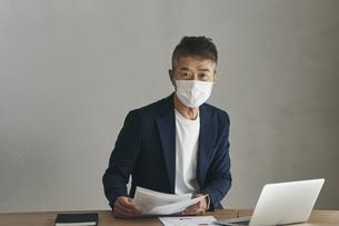 マスクをつけて仕事をする日本人シニア男性の写真素材 [FYI04774461]