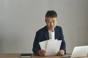 デスクワークをする日本人シニア男性の写真素材 [FYI04774462]