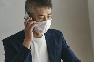 マスクをつけてスマートフォンで話す日本人シニア男性の写真素材 [FYI04774468]