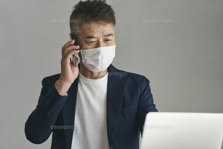マスクをつけてスマートフォンで話す日本人シニア男性の写真素材 [FYI04774470]