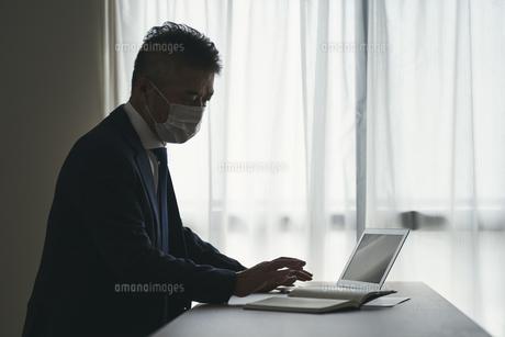 マスクをつけて仕事をするシニア世代の日本人ビジネスマンの写真素材 [FYI04774472]