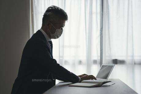 マスクをつけて仕事をするシニア世代の日本人ビジネスマンの写真素材 [FYI04774473]