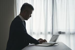 デスクワークをするシニア世代の日本人ビジネスマンの写真素材 [FYI04774474]