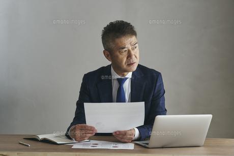 デスクワークをするシニア世代の日本人ビジネスマンの写真素材 [FYI04774475]