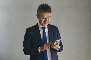 スマートフォンを見るシニア世代の日本人ビジネスマンの写真素材 [FYI04774490]