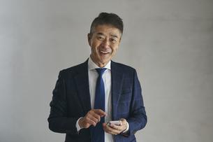 スマートフォンを持つ笑顔のシニア世代の日本人ビジネスマンの写真素材 [FYI04774492]