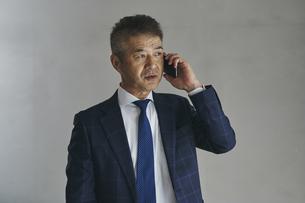 スマートフォンで話すシニア世代の日本人ビジネスマンの写真素材 [FYI04774493]