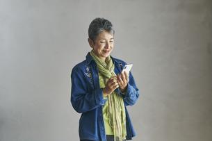 スマートフォンを見る日本人シニア女性の写真素材 [FYI04774497]