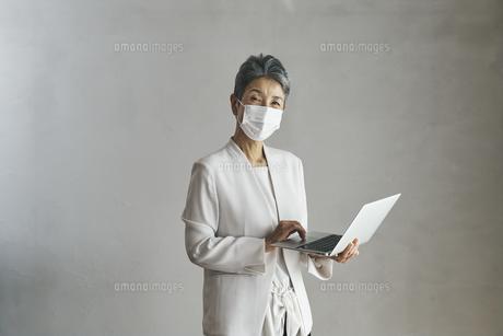 マスクをつけてノートパソコンを持つシニア世代の日本人キャリアウーマンの写真素材 [FYI04774498]