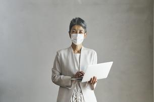 マスクをつけてノートパソコンを持つシニア世代の日本人キャリアウーマンの写真素材 [FYI04774499]