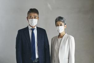マスクをつけたシニア世代のビジネスマンとビジネスウーマンの写真素材 [FYI04774502]