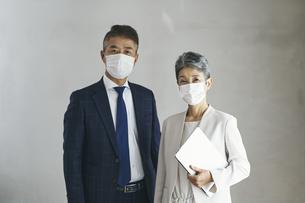 マスクをつけたシニア世代のビジネスマンとビジネスウーマンの写真素材 [FYI04774503]