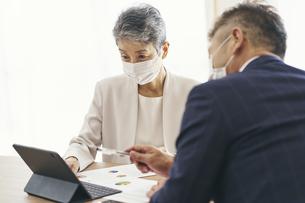 マスクをつけてミーティングをするシニア世代のビジネスウーマンの写真素材 [FYI04774508]