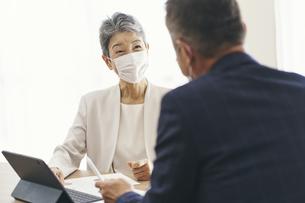 マスクをつけてミーティングをするシニア世代のビジネスウーマンの写真素材 [FYI04774509]