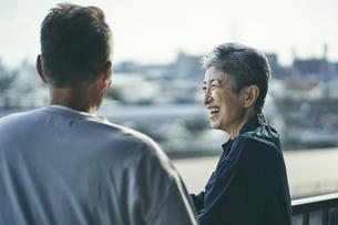 ベランダで景色を眺める笑顔の日本人シニア女性とシニア男性の写真素材 [FYI04774689]