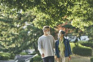マスクをつけて公園を散歩する日本人シニア夫婦の写真素材 [FYI04774700]