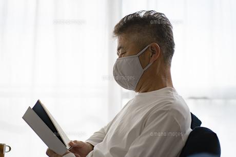 マスクをつけて読書をする日本人シニア男性の写真素材 [FYI04774725]